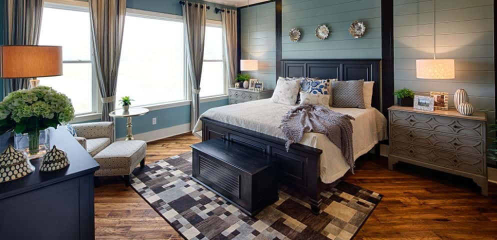 """The owner's retreat has a spa feel,"" Becker says.<br /> <br /> From the millwork walls to the cool blues and grays, the master bedroom is both spacious and relaxing. The diagonal flooring continues into the bedroom.<br /> <br /> PHOTO COURTESY OF<br /> Schumacher Homes"