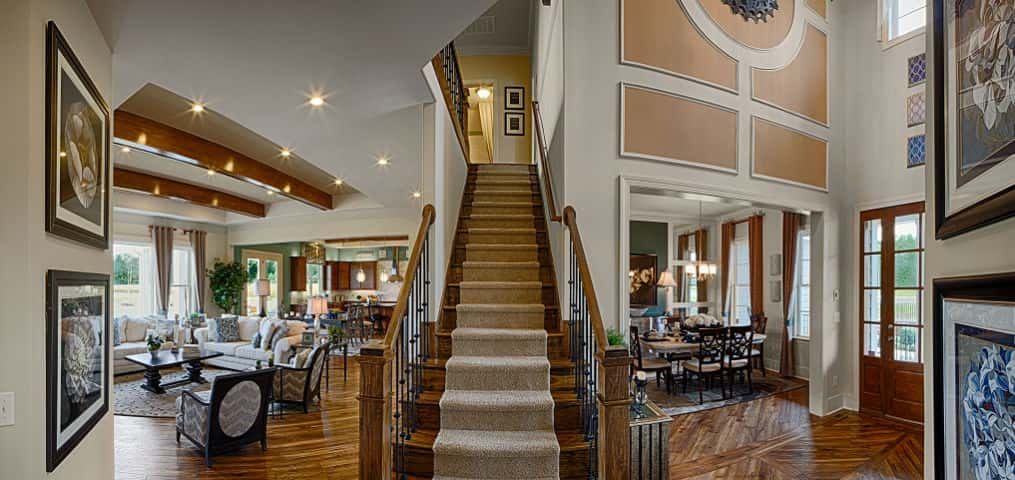 "Small ceiling lights twinkle in the great room while a high ceiling and lots of windows bring sunshine into the home's foyer. This panoramic shot shows just how the home's entryway and living spaces come together.<br /> <br /> Becker says the home's spacing gives it a grand feel. ""It feels so much larger than it is and it has a lot of features that are characteristic of a great home,"" Becker says of the two-story, 3,795-sq. ft. home.<br /> <br /> PHOTO COURTESY OF<br /> Schumacher Homes"