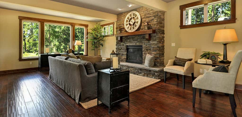 "<p>A stone fireplace and wood floors carry on the rustic feel in the home's living room while large windows keep the space from being too dusky or confining.<br /> <br /> ""Because of the open floor plan, we think it has a real nice flow to it,"" Atherton says. ""It's a very efficient plan and it lives very large.""</p> <p >PHOTO COURTESY OF<br /> The Burnsteads</p>"