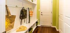 Into a tight and long mudroom white color of the furniture and doors provides the feeling of a larger space.