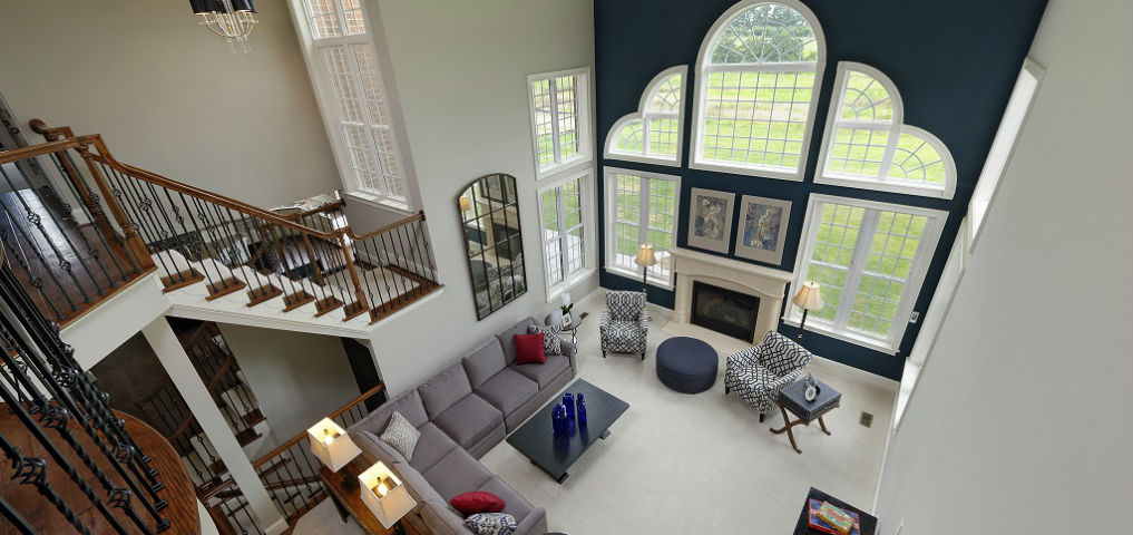 The wall of windows dominates the two-story family room, providing tons of natural light into the space and affording residents great views of the natural surroundings. The room can be viewed directly from the entry, creating a nice flow and brightness running the entire breadth of the house. Carpeting and a fireplace help anchor the living area where family and friends can gather to relax.<br /> <br /> PHOTO COURTESY OF<br /> Williamsburg Homes LLC
