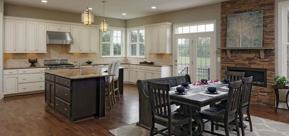 The open kitchen and breakfast area, including an optional morning room, is a perfect entertaining space for parties ranging from formal to casual or just for hosting family get-togethers. Standard features include maple wood cabinets with crown molding, Kitchen Aid stainless steel appliances, and granite countertops, but owners can choose from a variety of optional fixtures and appliances. The size and positioning of the large island is also flexible, allowing owners to create the most functional layout for their needs.<br /> <br /> PHOTO COURTESY OF<br /> Williamsburg Homes LLC