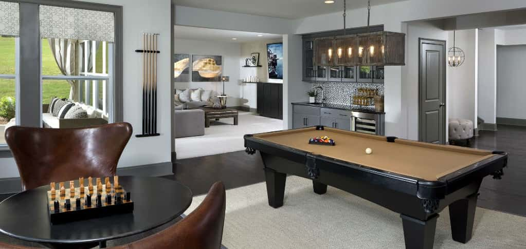 "Pool tables are a classic feature of game rooms and can make a space look very sophisticated. Game rooms don't just have to be for kids! This <a href=""https://www.newhomesource.com/plandetail/17623-hawkwatch-lane-charlotte-nc-28278/1262932"" target=""_blank"" title=""See More Photos of the Logan Plan by CalAtlantic Homes"">room </a>is styled as a cool hang out spot for adults, while still having a cozy feel to it. Friends and neighbors will want to come over every day once they see a pool table in your game room!<br /> <br /> <strong>Photo Courtesy of</strong><br /> CalAtlantic Homes"
