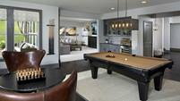 A basement game room in the Logan Plan by CalAtlantic Homes has a pool table and a wet bar. At Montage at Palisades - The Enclave in Charlotte, N.C.
