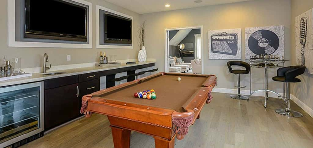 "Wet bars are amazing for game rooms, as they add the extra function of serving food and drinks to guests. Constantly running between the game room and the kitchen could keep you from fully enjoying your game night, so having a bar in the room will feel relaxing and luxurious. This <a href=""https://www.newhomesource.com/plandetail/7518-blue-quail-lane-orlando-fl-32835/1316061"" target=""_blank"" title=""See More Photos of the Tuscany Plan by Taylor Morrison"">long bar</a> has a built-in refrigerator, sink and space for tucked-in chairs. What a great place to host a party! <br /> <br /> <strong>Photo Courtesy of</strong><br /> Taylor Morrison"
