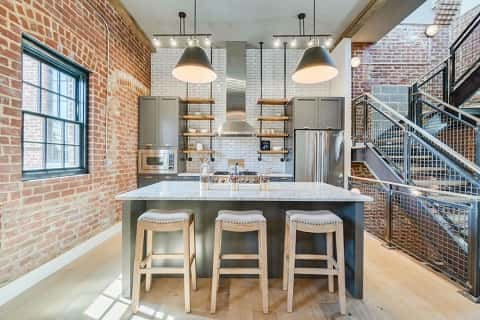 With stainless steel appliances, open cabinets made with metal pipes and wood, subway tile walls and exposed brick walls, this condo at the Helicopter Factory in Washington, D.C., breathes industrial style. Photo courtesy of HD Bros.