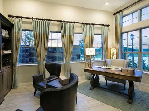A home office in the Beech plan by Meritage Homes is full of natural light, due to the plethora of windows in the space. A desk sits diagonally behind two leather wing back chairs. At the Hills at Legacy – Woodland Series in Prosper, Texas.