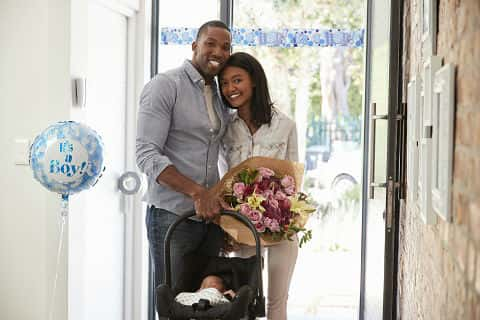 African American parents arriving home with newborn baby in car seat with balloon that says 'It's a Boy!'