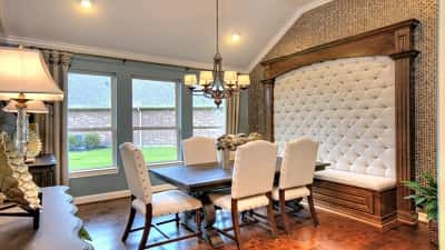 This model home at Bonterra at Woodforest in Montgomery, Texas, has space enough for a table with six five seats and a tufted headboard accent wall with bench.
