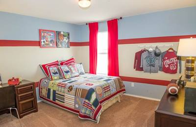 A blue, red and white color scheme highlights a football themed kids room in the Granville Plan at Southridge Crossing by Centex Homes in Houston.