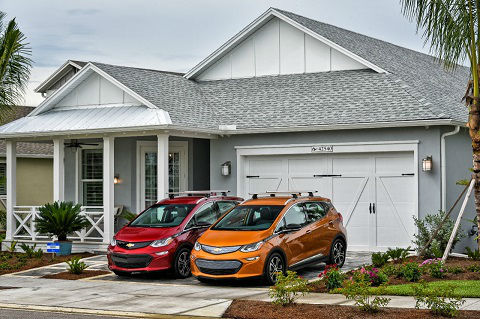A red and an orange Chevrolet Bolt sit in front of a new home at Babcock Ranch on Florida's Gulf Coast.