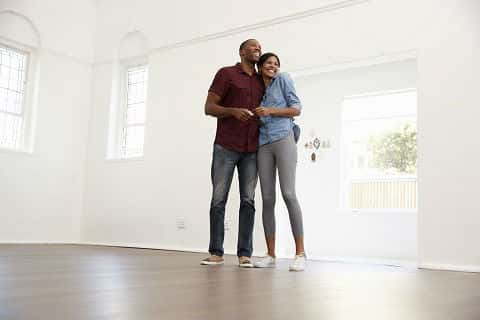A Millennial African America couple happily stands in the empty living room of their new home.