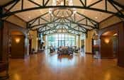 An exposed-beam ceiling creates a spacious and open environment for residents enjoying the community center at Frisco Lakes in Frisco, Texas.