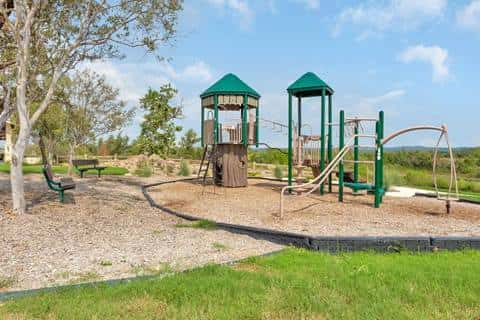 A fort-like playground at Talise de Culebra by LGI Homes as a fort, monkey bars and a spinner.