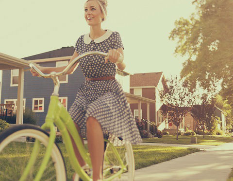 A female in a retro blue and white polkadot dress enjoys a ride on her vintage bike in the summer afternoon in the suburbs.