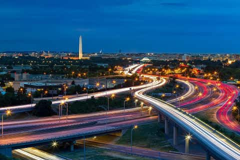 The Washington, D.C., cityscape at dusk, with rush hour traffic trails on I-395 highway. Washington Monument, illuminated, dominates the skyline.