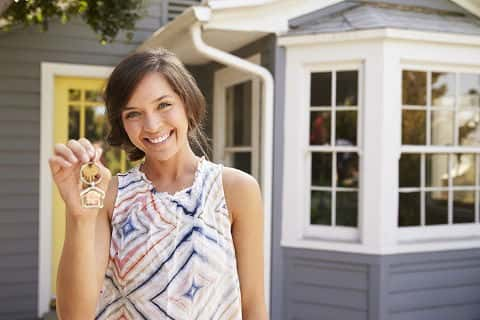 A young, single female stands outside her new home with the keys in her hand.