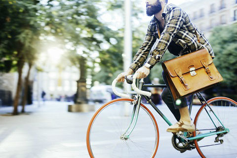 One young man speeding with his bike and commuting to work in the street of Barcelona.