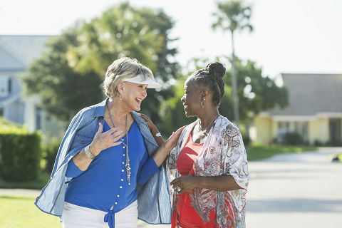 Two multi-racial senior woman, one Caucasian and the other African American, taking a walk in a residential neighborhood on a bright, sunny summer or spring day. They are enjoying each other's company, smiling, face to face, talking.