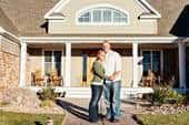 Happy homebuyer couple standing in front of new home with porch and brick and vinyl siding.