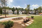 A walking trails winds around homes and a green space with picnic bench in Cresswind Charlotte, a community that appeals to 55+ homebuyers in Charlotte, NC.