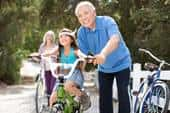 An older Asian man on a hike and bike trail helps his granddaughter ride her bicycle, while his wife stands by a bike in the background.