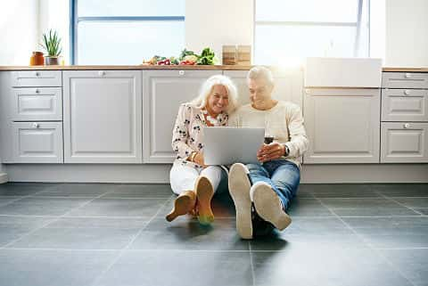 Smiling senior couple sitting on their kitchen floor at home drinking red wine and browsing the Internet on a laptop.