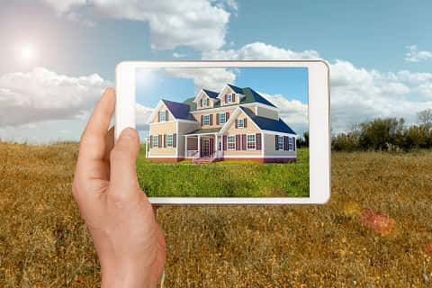 Hand holding a digital tablet showing the design of a new home over the place where the project will be realized, using technology and augmented reality. Country-style home planned to be built on a grass field. Forecasting and wishing a new dream home.