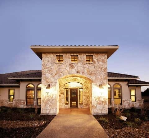 A stone exterior is magnified by a two-story porch that welcomes guests to this custom home in New Braunfels, Texas, by Sierra Classic Custom Homes.