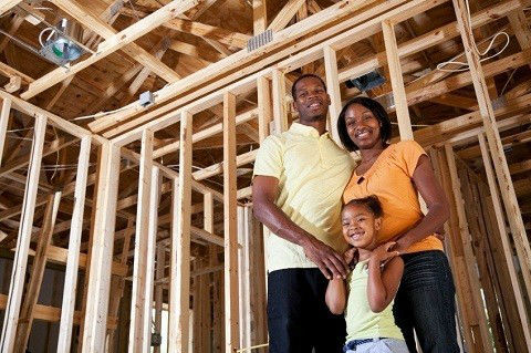 A young African American family stands in framed-out new home.