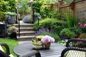 A backyard garden has a small wood deck with set of steps that lead to a sunken garden area with a wooden outdoor furniture set.