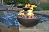 A combination of bronze and ice blue fire glass burns in an outdoor fire bowl.