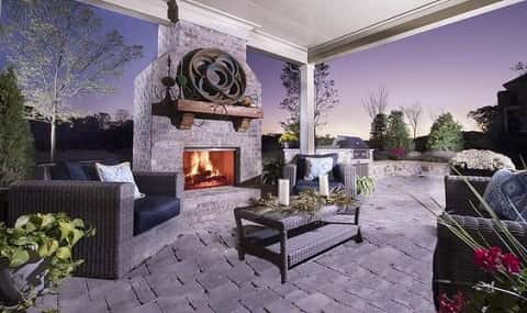 An outdoor space outside of this new home by FrontDoor Communities includes an outdoor fireplace to keep warm by during chilly days and nights.