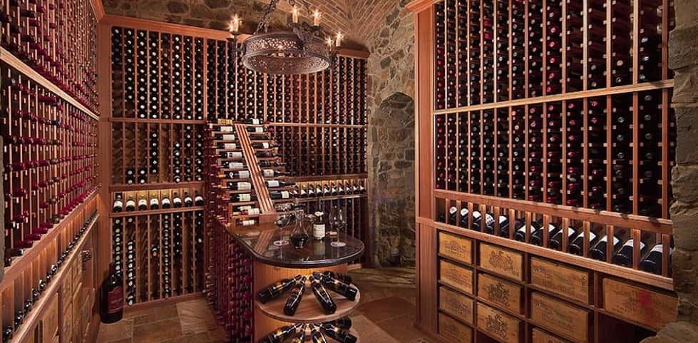 "The stars aligned perfectly in this remarkably beautiful wine cellar.<br /> <br /> Designed by Mark J. Karpinski of <a href=""http://wineracks.com/"" target=""_blank"" title=""WineRacks.com"">WineRacks.com</a> in collaboration with the homeowner and the homeowner's wine broker, this wine cellar evokes a traditional wine cave through the use of stone and brickwork and special touches like the metal chandelier.<br /> <br /> To hold this 2,000-plus bottle collection, classic mahogany wine racks and special wine case shelving line the room, lead to the cellar's centerpiece: a waterfall and marble tasting table with rounded display shelves. <br /> <br /> PHOTO COURTESY OF<br /> WineRacks.com"