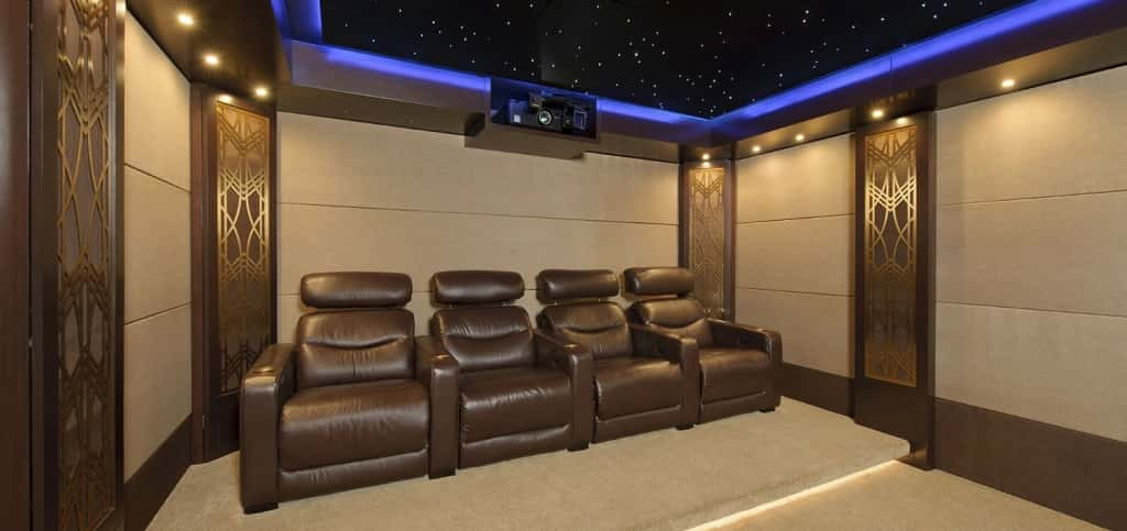 "Decorative speaker grills reminiscent of the Empire State Building's Art Deco interior lends this home theater its ""Manhattan Project"" theme.<br /> <br /> Designed by Houston-based Caveman Home Theaters, the space includes a 135-inch motorized film screen and a 3-D projector. A fiber-optic ceiling and blue LED lighting create the feel of a rooftop theater, while the soundproofed walls, ceiling and floor ensure all of the movie noise stays where it should — in the theater.<br /> <br /> PHOTO CREDIT:<br /> Caveman Home Theaters"