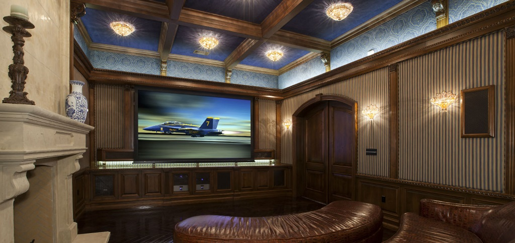 This home theater from Bliss Home Theaters and Automation in Los Angeles blends timeless elegance with state-of-the-art electronics to create a warm and versatile space for the homeowners.<br /> <br /> A rich brown leather couch and divan next to a grand fireplace create the perfect atmosphere for settling in to watch a movie. A coffered ceiling with beautiful lighting fixtures that give off a soft glow — along with the wall sconces — add to the inviting atmosphere.<br /> <br /> PHOTO CREDIT:<br /> Bliss Home Theaters and Automation