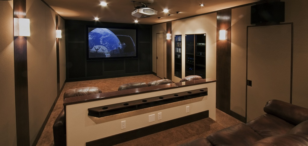 Built in the home's walkout basement, this Colorado home theater designed by Custom Quality Theaters blends well with the rest of the house while paying attention to the details, such as the lighting, the use of cherry trim around the room and movie poster alcoves.<br /> <br /> Hidden speaker enclosures and a hidden gear access room make creative uses of the space, allowing more room for family and friends to enjoy a fun and comfortable night at the movies.<br /> <br /> PHOTO CREDIT:<br /> Custom Quality Theaters
