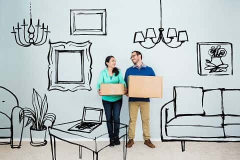 Mid adult Hispanic couple imagine their house as they stand in an empty living room. Digital artwork imposed on the photo includes picture frames, sofa, chair, coffee table with laptop and lighting equipment. The couple hold boxes and are looking at one another as they daydream.