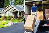 Photo of a mover unloading truck, walking cardboard boxes down ramp on a hand truck, in front of a new home.