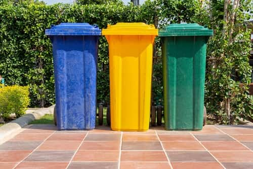 Colorful trash and recycling bins outside. Photo courtesy of GettyImages/PakinSongmor.