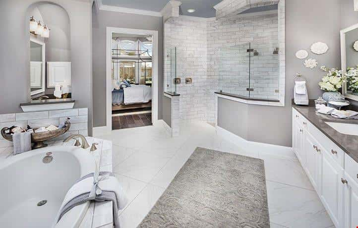The spacious gray and white master bathroom in the Tillman plan by Village Builders in Friendswood, Texas, features a stone and glass-encased walk-in shower, soaker tub and double vanities with lots of counter space and cabinet storage.