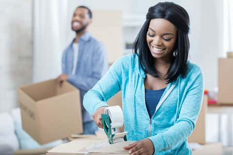 Focus in on close up of a smiling young African American woman as she finishes taping up a moving box. Her smiling husband is in the background carrying a donations box.