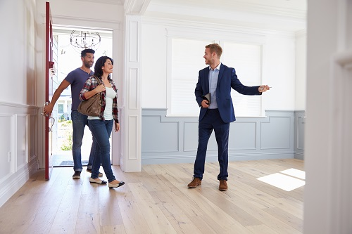 Couple looks through home with a Realtor.
