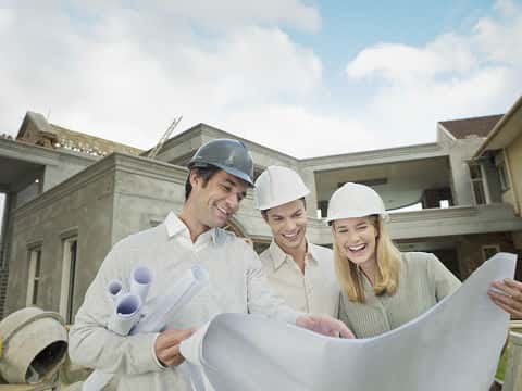 An architect and couple wearing hard hats look at floor plans outside their new home that is under construction.