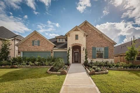 Stone and brick siding are a classic touch to this Craftsman-style home by David Weekley Homes at the Hills of Westlake 60' in Conroe, TX.