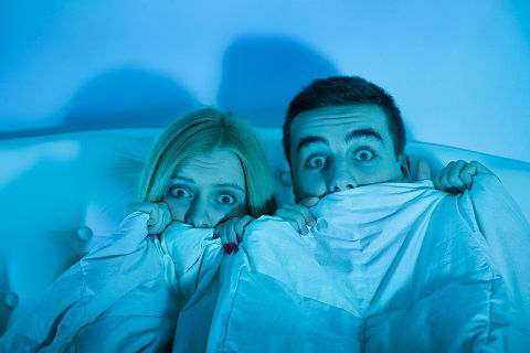 Frightened couple hiding under the covers with their eyes peeking out after learning of all the problems with their old home.