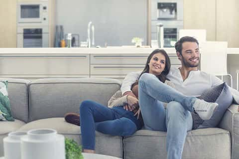 Portrait of couple relaxing on the sofa. They are cozy in a luxury home. Both are casually dressed and embracing. There is a modern kitchen in the background.