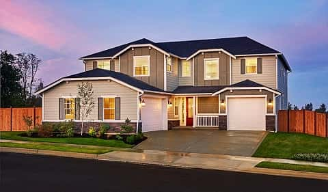 The exterior of the Daley plan by Richmond American Homes features a blue roof, white vinyl siding with stone accents and two garages. A red front door greets guests on a porch. Located at Retreat at Sunshine in Puyallup, WA.