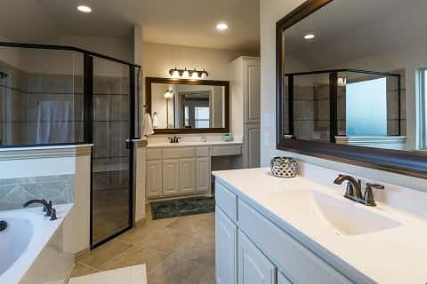 A glass-encased walk-in shower sits next to a soaker tub in the master bathroom of a new home by Riverside Homebuilders at Innisbrook Place in Fort Worth, Texas.