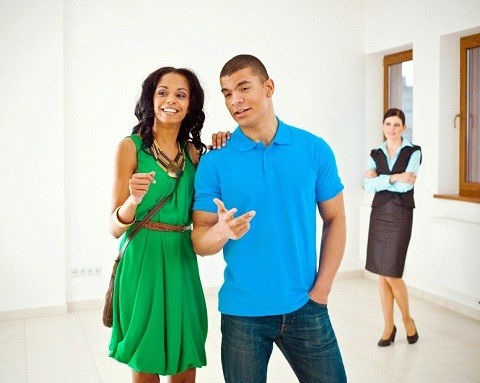Young African-American couple viewing a model home with an on-site sales staffer in the background.